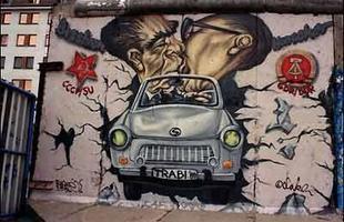 Neste grafite mais ousado Leonid Brezhnev e Erich Honecker, respectivamente dirigentes da URSS e RDA, se beijam apaixonadamente em um Trabant