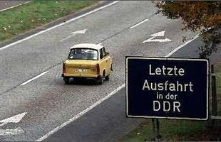 Placa indicando: última saída a esquerda na Alemanha Oriental.