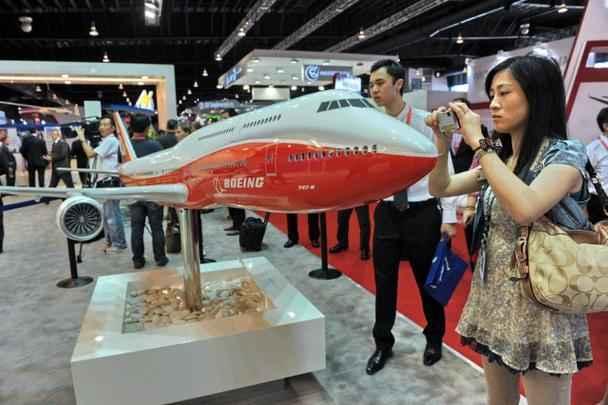 Visitantes da feira fotografam o novo Boeing 747-800