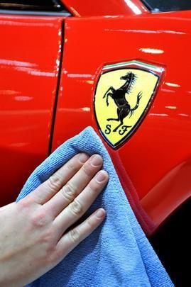 Funcionários limpam a Ferrari para a chegada dos jornalistas