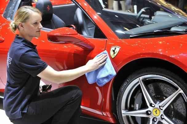 Fuincionários limpam a Ferrari para a chegada dos jornalistas