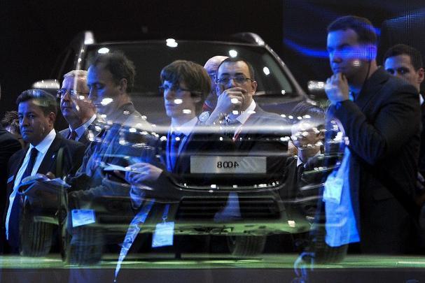 Jornalistas observam o reflexo do Peugeot 4008