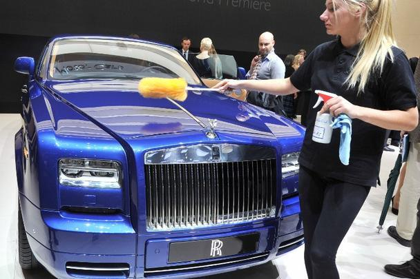 Funcionária do salão limpa um Rolls Royce no estande da marca