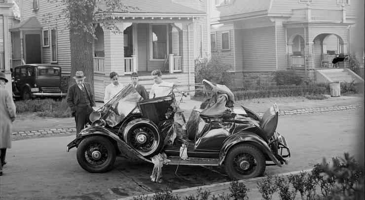 Homens param para olhar um veículo acidentado em uma rua residencial