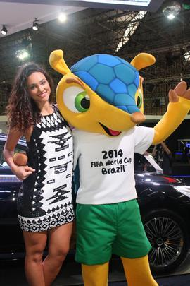 A atriz Debora Nascimento com o mascote da copa 2014 no estande da Kia