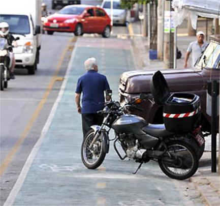 Na Rua Professor Moraes, moto e carro estacionados na ciclovia