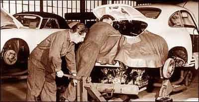 Nas instalações da fábrica da Porsche, em 1960, funcionários instalam o motor no 356 -