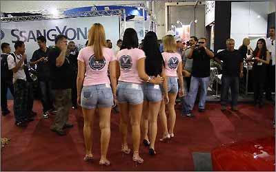 Garotas da revista Auto Som desfilam pelo evento de estande em estande -