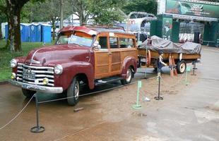 Caminhonete Chevrolet Woody carregando uma lancha também feita de madeira