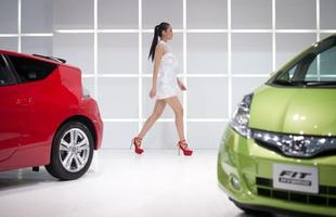 Modelo ao lado de um Honda Fit