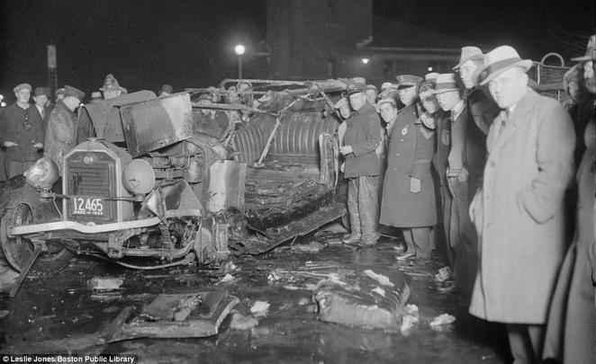 População de Boston posam para foto ao lado de um veículo queimado, em 1933