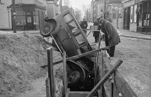 Pedestres tentam descobrir como este carro foi parar com a frente dentro da vala. O monte de terra acumulada ao lado já dá uma dica