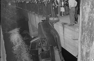 Em 1934, um veículo utilitário fica equilibrado em apenas uma roda. Funcionários de uma fábrica de chocolates em frente correm para ver a cena